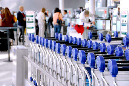 Luggage carts at modern international airport passengers at check-in counter in the background photo