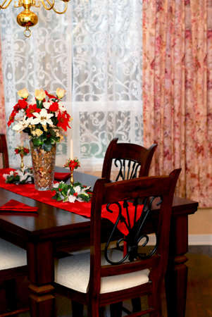window curtains: Dining room decorated for Christmas celebration, focus on the front chair Stock Photo