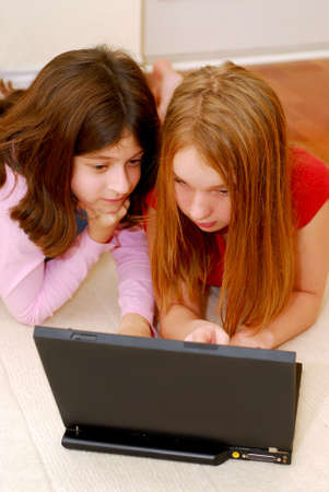 Portrait of two girls lying on the floor and  looking into computer photo