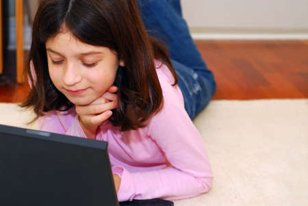 Portrait of a young girl lying on the floor and looking into computer photo