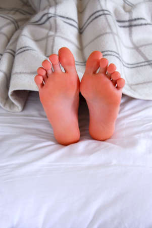 feet in bed: Childs feet sticking out of a blanket in a bed