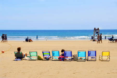 scenical: A row of colorful folding chairs on a sandy beach Stock Photo