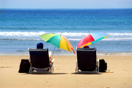 folding chair: A couple relaxing on a beach under colorful umbrellas