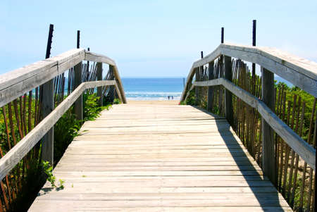 Wooden path over sand dunes with ocean view photo