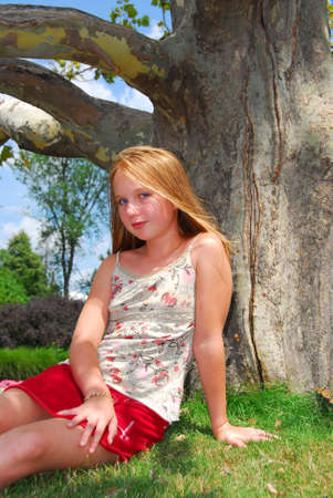 Young girl sitting under old big tree in the summer Foto de archivo