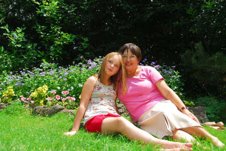 boomer: Portrait of grandmother and granddaughter in a garden