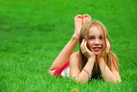 sun down: Young girl lying on green grass in the summer