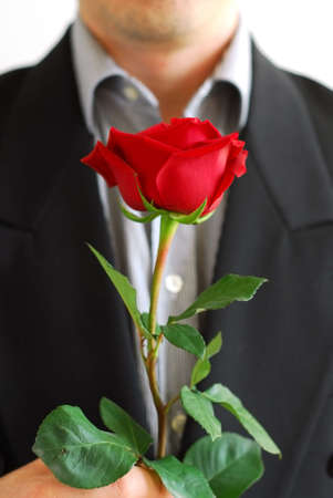 Man in black suit holding a red rose Foto de archivo