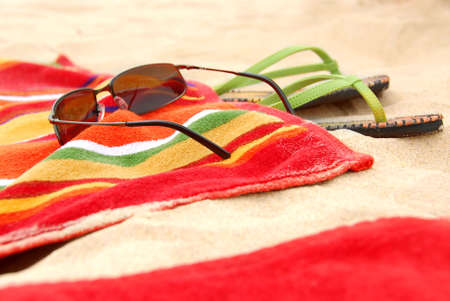 Bright colorful towels and other beach items on a beach