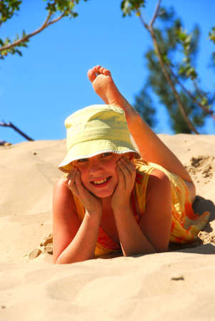 preteens beach: Young girl in yellow hat lying on top of a sand dune