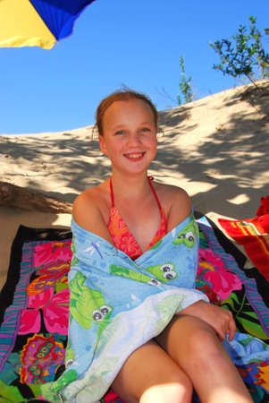 Young girl sitting on a beach wrapped in towels after swimming Foto de archivo