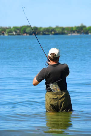 Man fishing in a lake standing in water photo