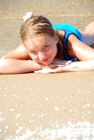 浅い水の中のビーチで横になっている若い女の子