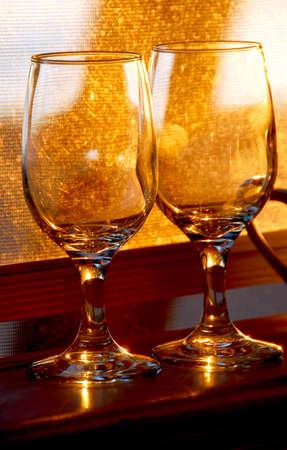 Two empty wine glasses reflecting sunlight on windowsill
