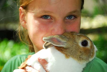 ni�as sonriendo: Retrato de una muchacha joven que sostiene un conejito afuera Foto de archivo