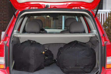 Red hatchback car loaded with open trunk and luggage photo