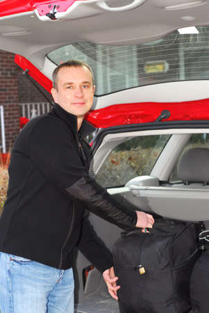 Man loading bags in the trunk of his car photo