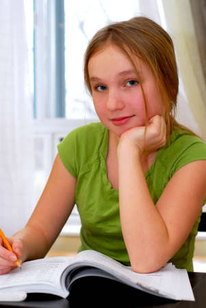 educational problem solving: Young school girl doing homework at her desk