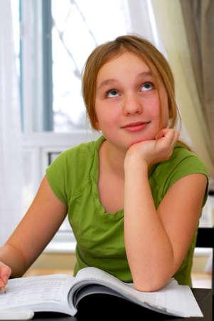 Young school girl doing homework at her desk