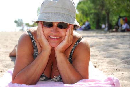Mature woman in sunglasses lying on a sandy beach photo