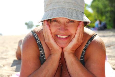 Mature woman lying on a sandy beach photo