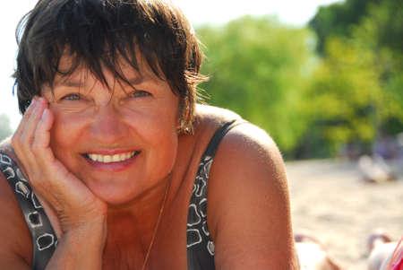 personas banandose: Retrato de una mujer madura que miente en una playa arenosa Foto de archivo