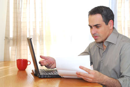 Man sitting at his desk with a laptop looking at bills Archivio Fotografico