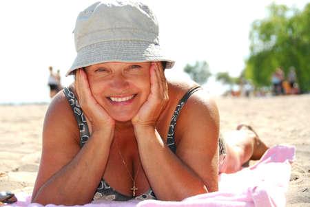 personas banandose: Mujer madura que miente en una playa arenosa