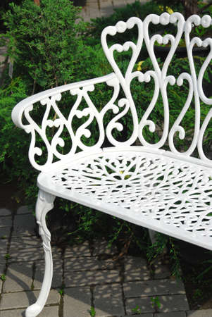 White wrought iron bench in a garden photo