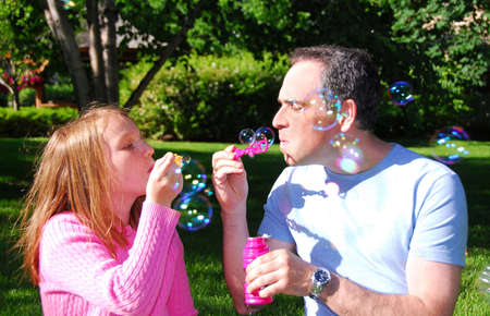 Father and daughter blowing soap bubbles together photo