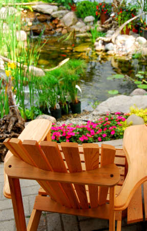 Natural stone pond and wooden patio chair as landscaping design element Imagens