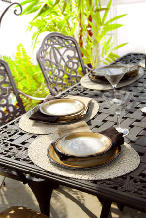 placemats: Table setting on a patio table with plates and martini glasses