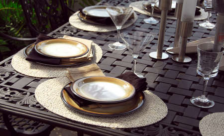Table setting on a patio table with plates and martini glasses