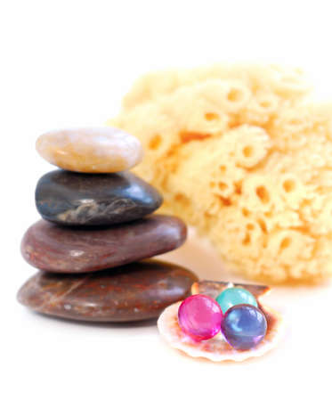 Stack of balanced stones with bath beads isolated on white background