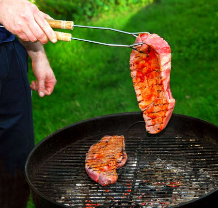 A man grilling beef stakes on outdoor barbecue photo