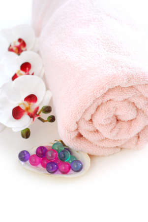 Pink rolled up towel with bath beads on white background