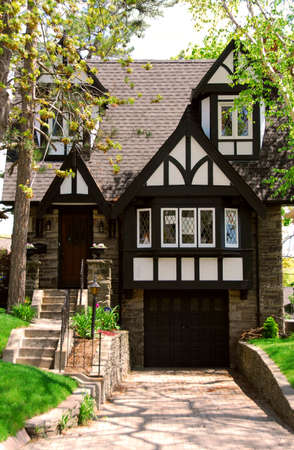 Residential tudor style house with green trees photo