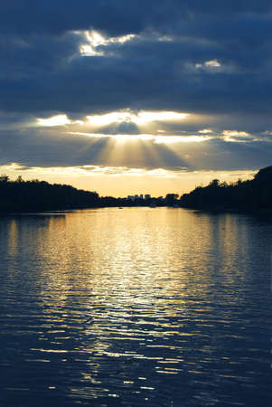 shining through: Raggi del sole che splende attraverso le nuvole e acqua tramonto
