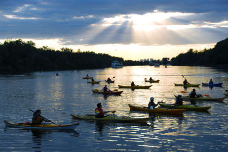 Group of people canoeing at sunset with sunrays shining through clouds Imagens