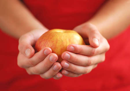 Childs hands holding an apple on red background