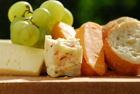cheeses: Assorted cheeses with grapes and white bread