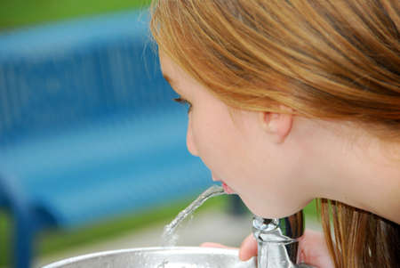preteen  pure: Young girl drinking water from a water fountain in a park