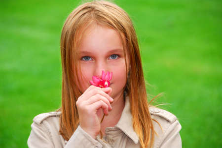 preteen  pure: Young girl holding a pink flower in her hand