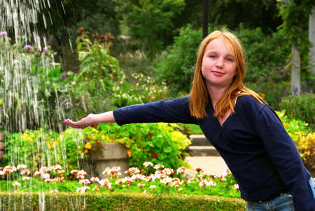 Young girl holding her hand under falling water in a garden photo