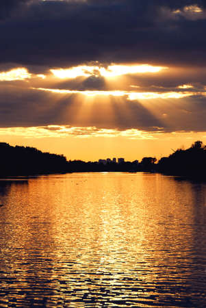 Rays of sun shining through the clouds and sunset over water photo