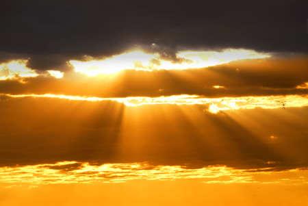 照らす: 夕焼け雲の切れ間から輝く太陽の光線 写真素材