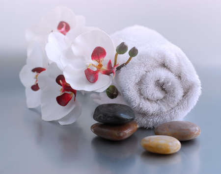 White rolled up towel with massage stones and an orchid Stock Photo - 737836