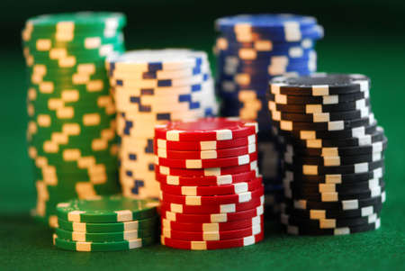 Stacks of gambling chips on green background photo