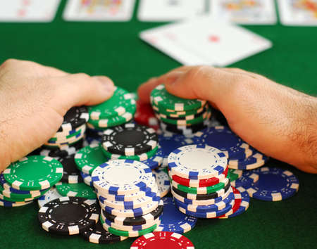 poker cards: Poker player raking a big pile of chips