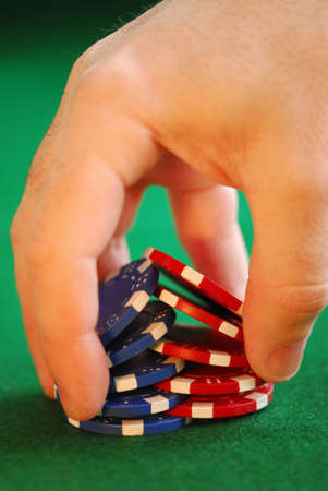 high stakes: Close up on mans hand doing a pocker chip trick shuffle